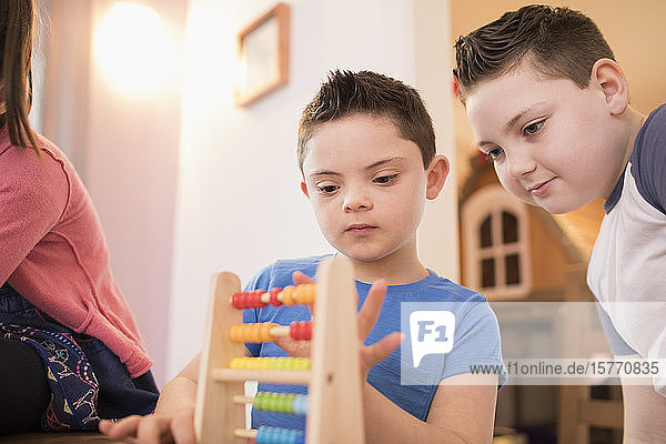 Boy with Down Syndrome and brother playing with toy