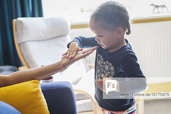 Curious girl touching hand of mother