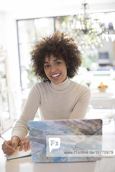 Portrait happy young female freelancer working at laptop
