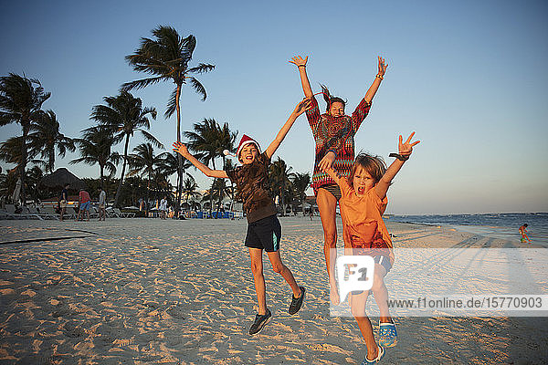 Portrait carefree family jumping for joy on tropical beach Mexico
