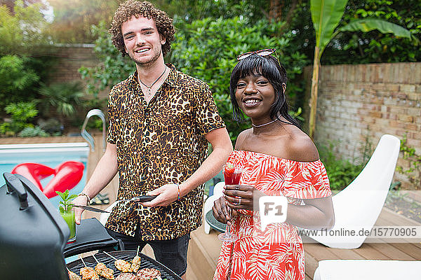 Portrait happy young couple barbecuing at poolside