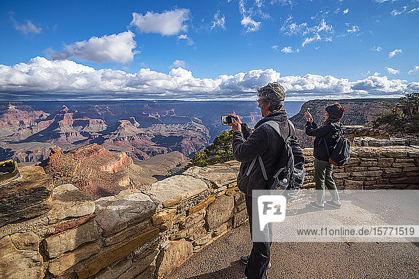 Tourists taking photos of the views of the Grand Canyon from the Rim Trail near the Village  Grand Canyon National Park; Arizona  United States of America