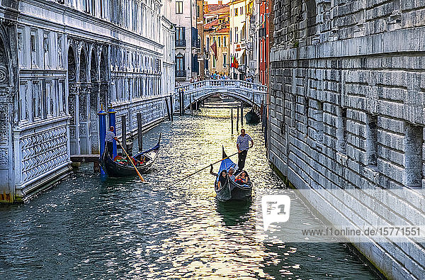 Gondola and gondolier with tourists in a canal; Venice  Italy