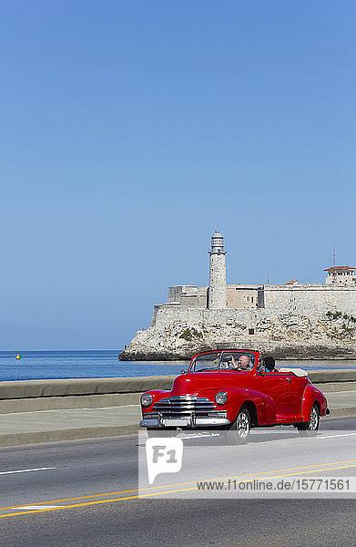 Old classic red convertible car on the Malecon  Castillo del Morro (background); Havana  Cuba