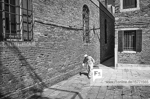 Man rolls a suitcase beside the brick wall of a building; Venice  Italy