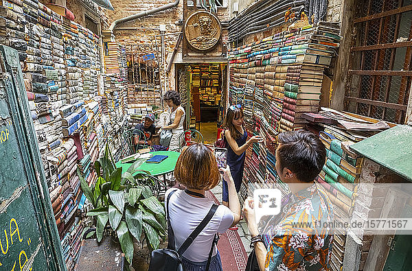 A tourist photographs a woman picking a book from the stacks of books in a shop; Venice  Italy