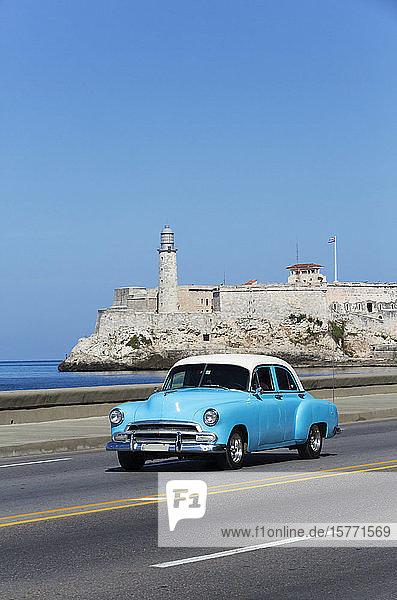 Old classic car on the Malecon  Castillo del Morro (background); Havana  Cuba