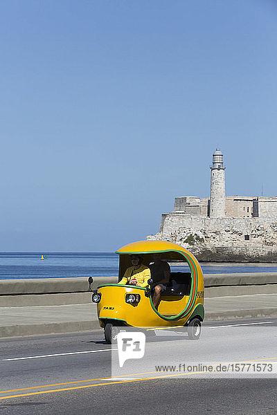 Yellow Cocotaxi on the Malecon  Castillo del Morro (background); Havana  Cuba