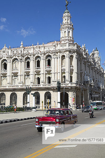 Grand Theater of Havana with old classic car driving on the street  Old Town; Havana  Cuba