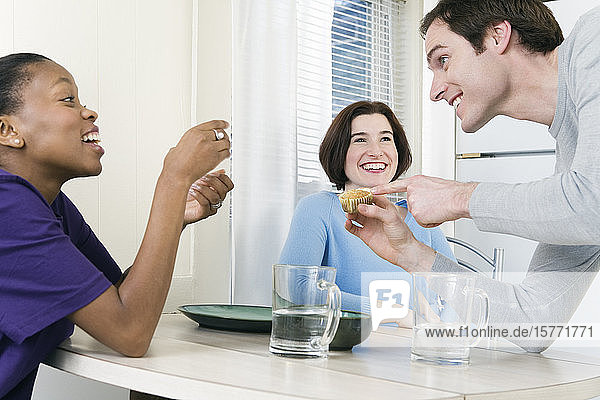 Man showing muffin to two women at dining table.
