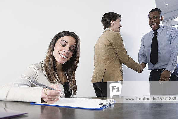 Business woman writing with business colleagues shaking hands in background.