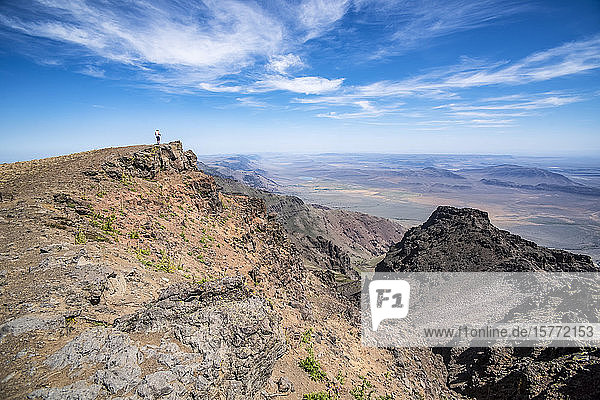A woman looking out across the Alvord Desert from a cliffs edge on Steens Mountain  Southeastern Oregon; Frenchglen  Oregon  United States of America
