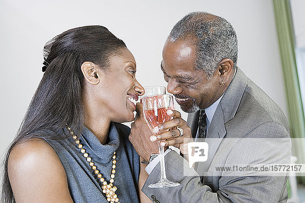 Close-up of a middle-aged couple toasting with wine glasses and smiling
