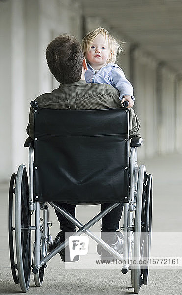 Man on wheelchair playing with baby