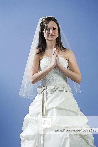 Portrait of bride joining hands.