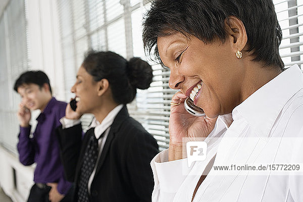 Business executives using Cellphones.