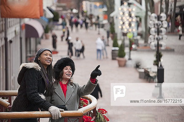 Two women standing on a balcony with Christmas decorations looking out at the city; Boston  Massachusetts  United States of America