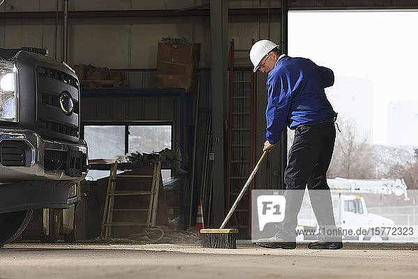 Man sweeping mechanic's workshop with a broom