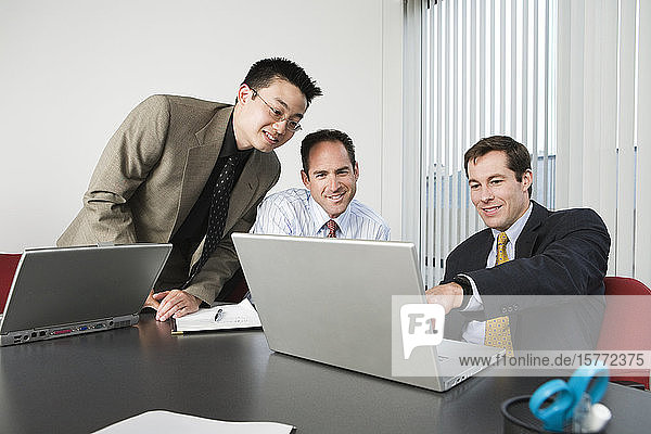 Businessmen looking at a laptop.