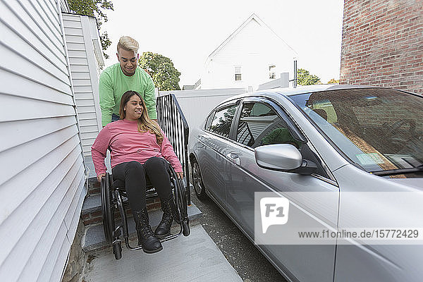 Man assisting a woman who has Spinal Cord Injury getting into her car