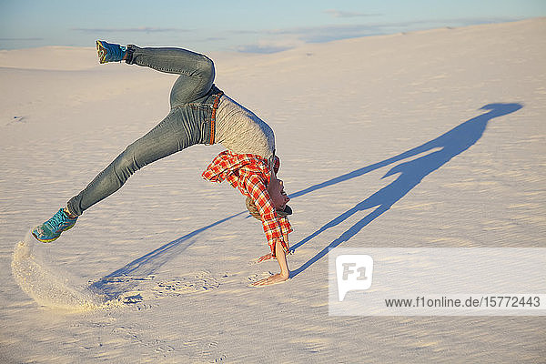 A young woman does a acrobatic move on the white sand with blue sky  White Sands National Monument; Alamogordo  New Mexico  United States of America