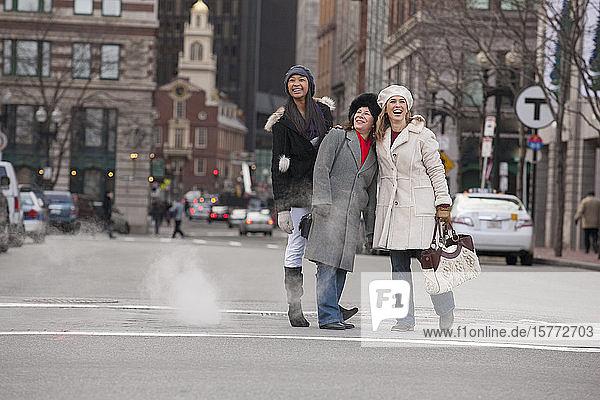 Three women standing on a city street; Boston  Massachusetts  United States of America