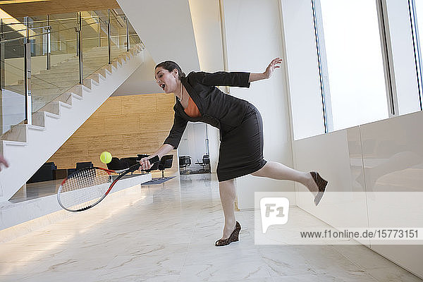 Businesswoman playing tennis in an office.