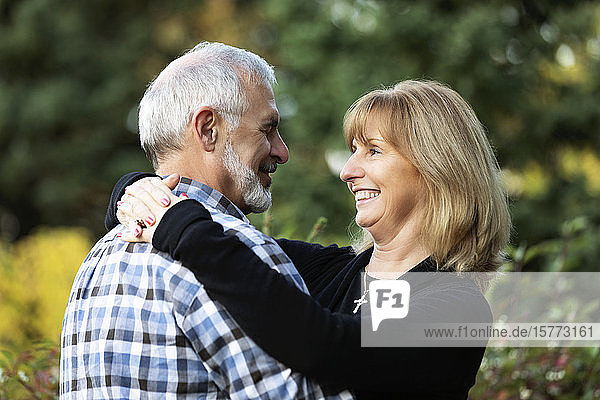 A mature couple enjoying time together  hugging and looking at each other in a city park on a warm fall evening; St. Albert  Alberta  Canada