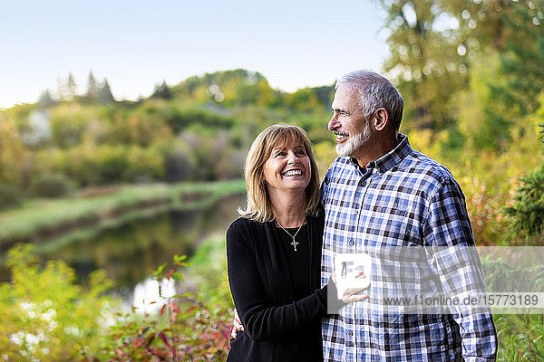A mature couple enjoying quality time together while walking along a river in a city park on a warm fall evening; St. Albert  Alberta  Canada