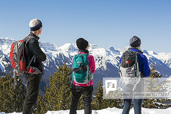Hikers overlooking a snow-covered mountain range and blue sky  Banff National Park; Banff  Alberta  Canada