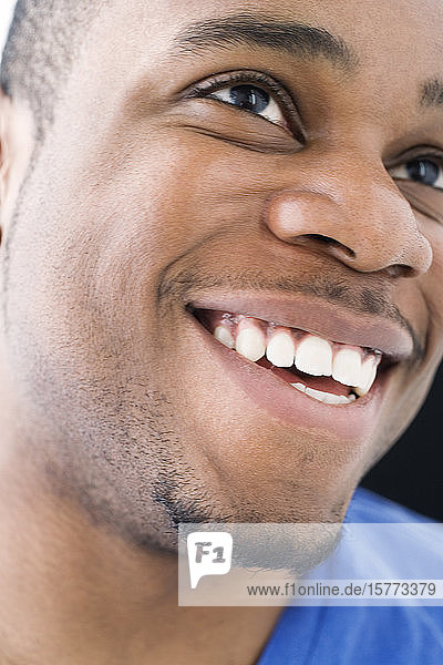 Close up of a young man smiling.