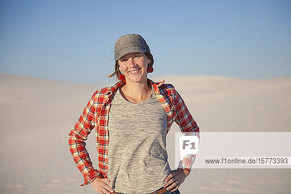 Portrait of a young woman standing on the white sand with blue sky  White Sands National Monument; Alamogordo  New Mexico  United States of America