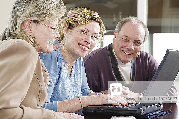 View of friends looking at a laptop.