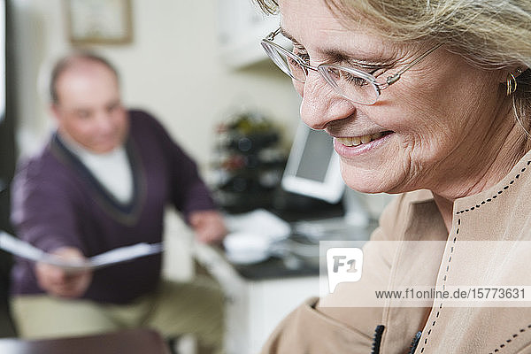 Close up of a smiling mature woman with mature man sitting in the background.