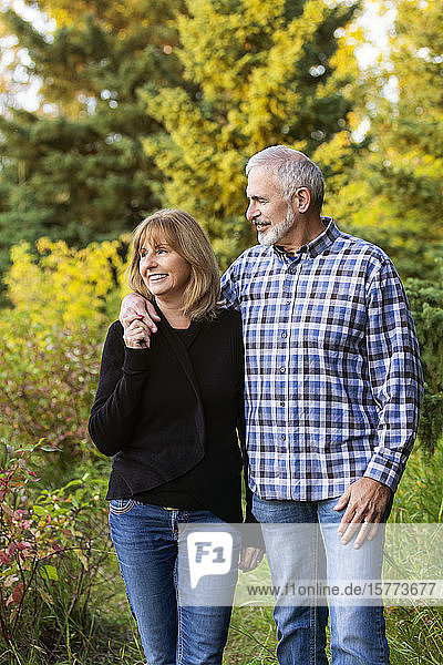 A mature couple enjoying quality time together while walking in a city park on a warm fall evening near dusk; St. Albert  Alberta  Canada