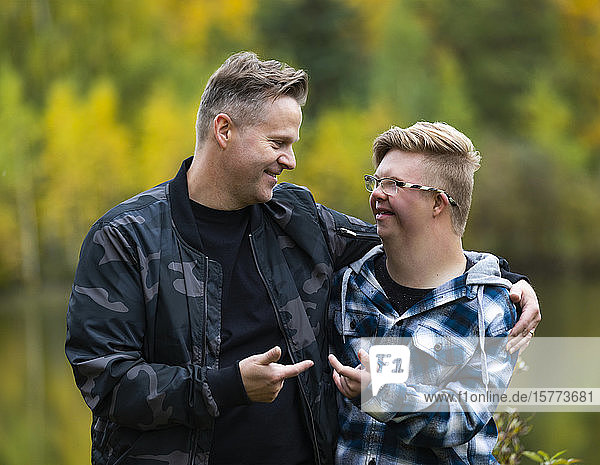 A young man with Down Syndrome and his father enjoying each other's company and giving each other funny hand gestures in a city park on a warm fall evening: Edmonton  Alberta  Canada