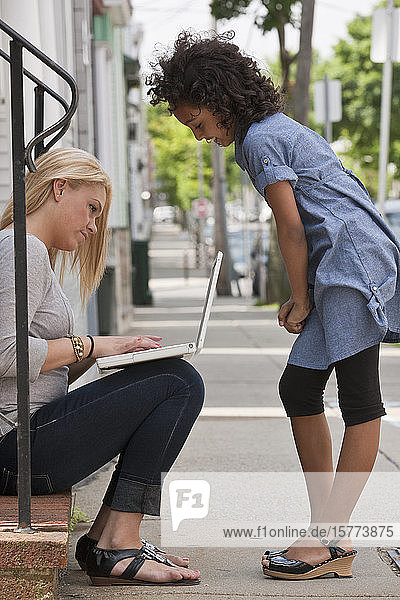 A young woman sits with a laptop computer as a young girl looks on
