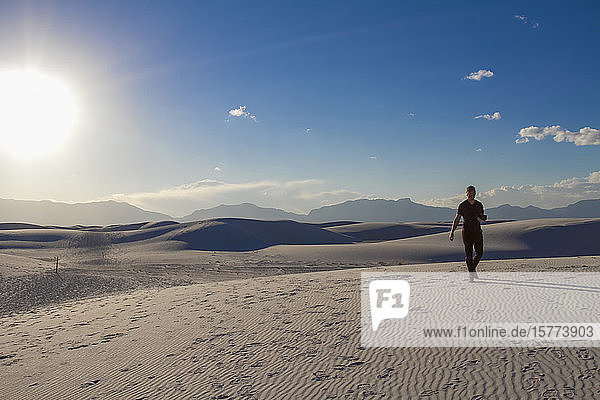 Male photographer walks with camera on the white sand  White Sands National Monument; Alamogordo  New Mexico  United States of America