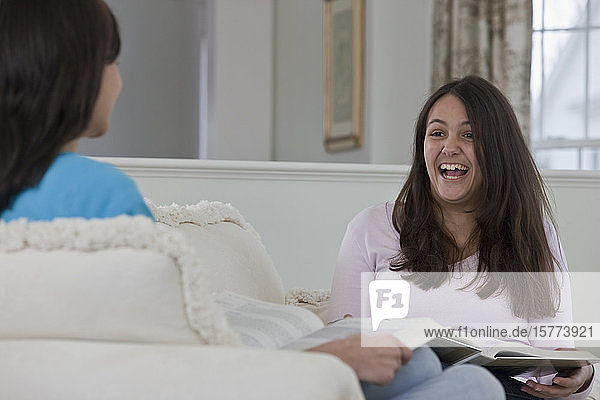 Two teenage girls sit on a couch looking at books and laughing together