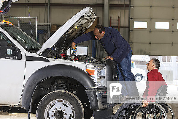 Vehicle mechanic working on a truck and man in wheelchair watching him work