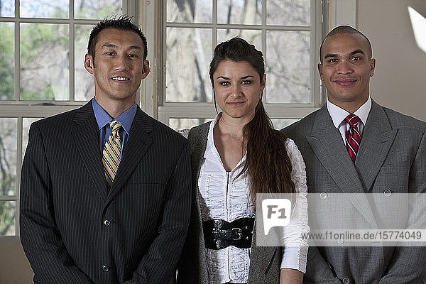 Portrait of three young professionals standing in a row
