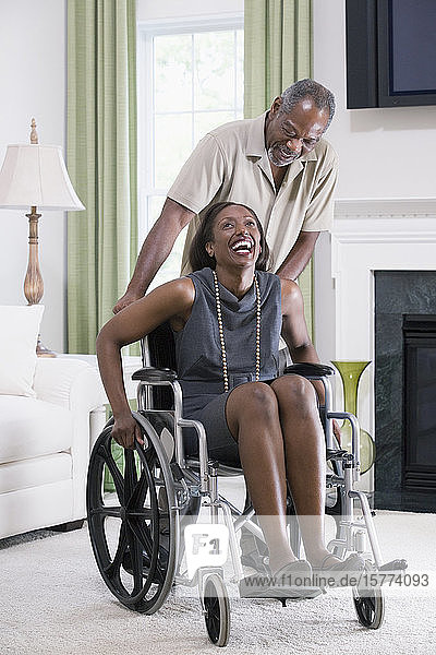 Middle-aged woman sitting in a wheelchair with a middle-aged man standing behind her