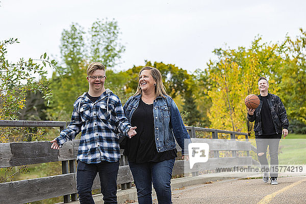 A young man with Down Syndrome walking with his father and mother while enjoying each other's company in a city park on a warm fall evening: Edmonton  Alberta  Canada