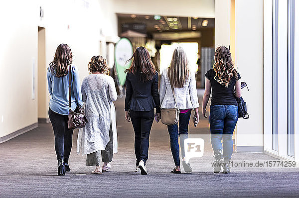 A view from behind of a group of women waliking down a hallway in a place of business: Edmonton  Alberta  Canada