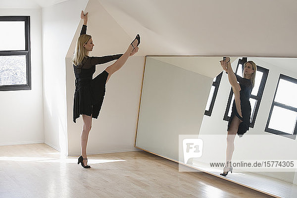 Mid adult woman dancing in front of a mirror