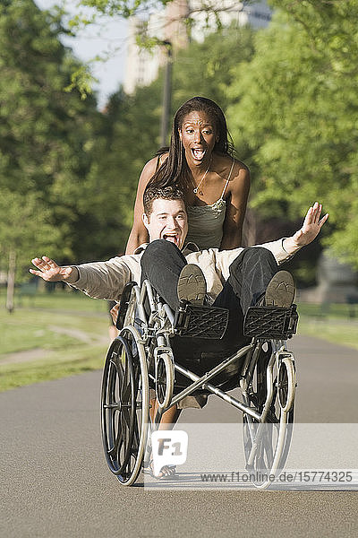 Mid adult woman pushing a mid adult man sitting in a wheelchair