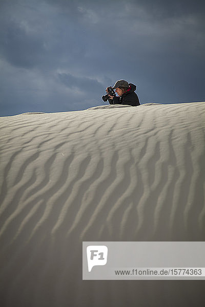 Female photographer takes a picture with white sand in the foreground  White Sands National Monument; Alamogordo  New Mexico  United States of America