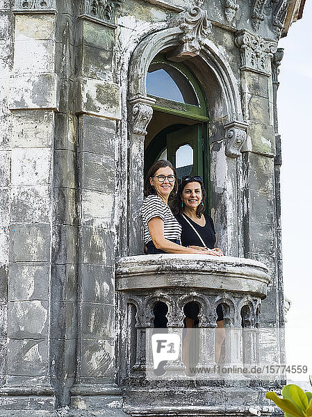 Two women stand on the balcony of an old building looking at the camera; Havana  Cuba
