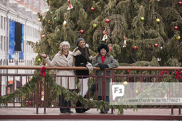 Three women standing on a balcony with Christmas decorations looking at the camera; Boston  Massachusetts  United States of America
