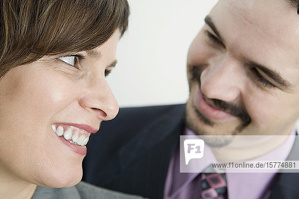 Close-up of a businessman and a businesswoman smiling together